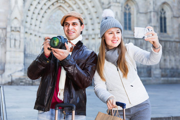 Couple man and woman in the historic center with camera and phone