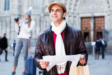 Male tourist standing with map