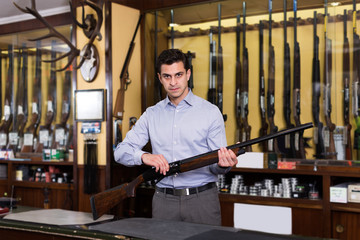 Adult male owner of hunting shop standing with shotgun