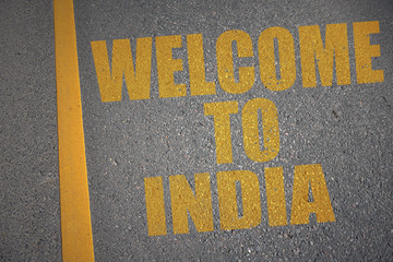 asphalt road with text welcome to india near yellow line.