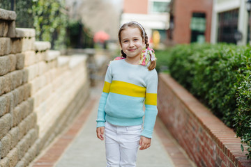 Cute young girl in pig tails looking at the camera