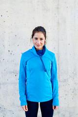 Beautiful smiling sportswoman in blue running longsleeve.