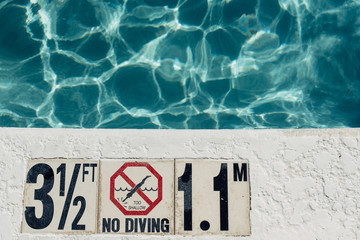 Shallow water warning sign by a pool