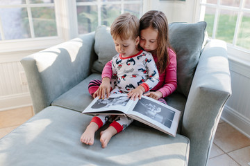 Little brother looking at a photo album with his big sister