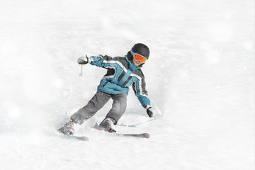 The boy in a blue jacket on skis in mountains