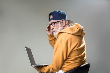 Advanced senior with pensive face looking at computer screen that is in hands. Isolated on grey background