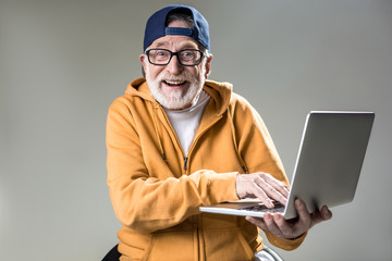 Waist up portrait of trendy pensioner enjoying the use of new laptop. He is looking at camera with big smile. Isolated on grey background Fotoväggar