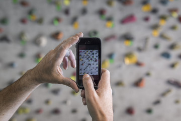 Taking a picture of the boulder wall with a mobile phone after workout