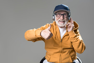 Waist up portrait of satisfied senior sitting on chair and enjoying music. He is looking at camera with broad smile. Isolated on grey background