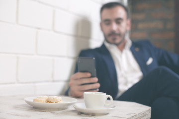 Morning coffee and cookies. Businessman sitting by the cafe table using mobile phone.