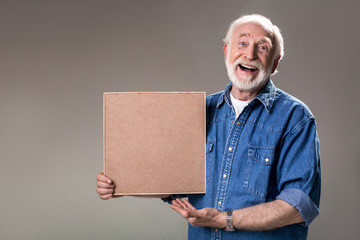 Waist up portrait of contented greybeard holding photograph and laughing. Isolated on grey background