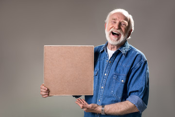 Waist up portrait of happy aging man holding wooden frame, his face expressing unbridled joy. Isolated on grey background