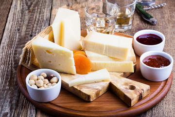Cheese platter with fruit jam, nuts and wine