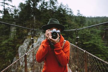 portrait of  a latin man taking a photo in a bridge