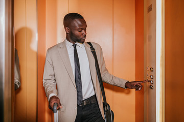 Elegant african businessman in the elevator pushing a button