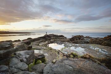 A lone figure on a rocky coast at dusk