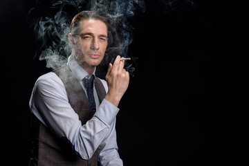 Feeling relaxed. Portrait of young serious man in formal clothes is standing and smoking cigarette. He is looking at camera confidently. Isolated background with copy space in the right side