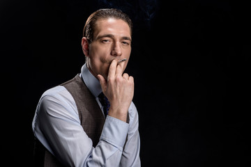 Breathe of male spirit. Stylish elegant attractive businessman is standing and holding cigarette in his mouth and smoking. He is looking at camera seriously. Isolated with copy space in the right side