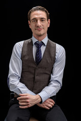 Successful career. Portrait of stylish attractive young businessman wearing official clothes is sitting and looking at camera confidently. Isolated on black background