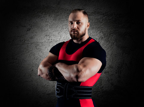 The weightlifter stands in a menacing pose with crossed huge arms
