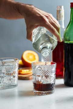 bartender pouring vermouth into glass with gin.