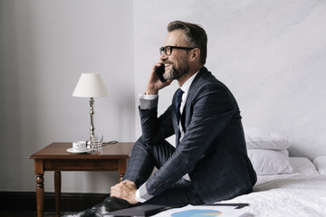 Smiling businessman in hotel room talking on Phone