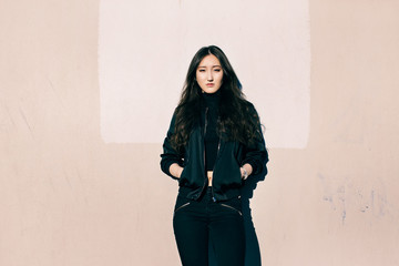 Portrait of Young Asian Woman in Black Bomber Jacket in Front of Pink Wall