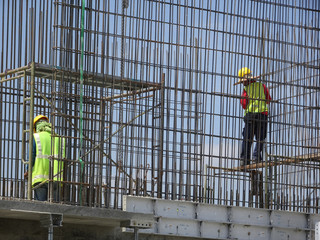 Construction workers fabricating steel reinforcement bar at the construction site. The reinforcement bar was tied together using tiny wire.