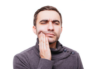 Closeup portrait of young man with tooth ache crown problem about to cry from pain touching outside mouth with hand, isolated on white background. Negative human emotion facial expression feeling