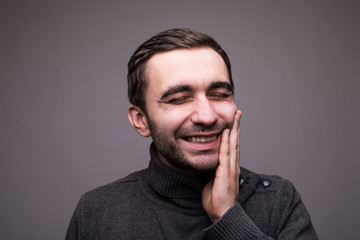 Closeup portrait of young man with tooth ache crown problem about to cry from pain touching outside mouth with hand, isolated on dark background. Negative human emotion facial expression feeling