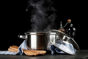 Steaming pot on black background
