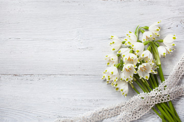 Snowdrop bouquet on a wooden background and lace ribbon