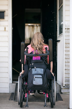 Young Girl In Wheelchair About To Enter House