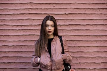 Portrait of beautiful woman in pink jacket standing against pink wall
