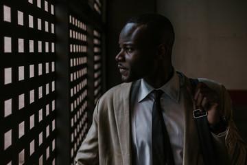 African American Businessman looking through a garage door