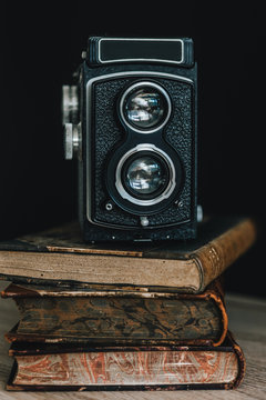Old camera over stack of books