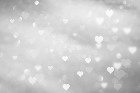 Beautiful abstract white colored hearts on blurry silver bokeh background.