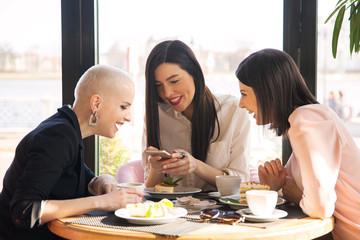 Three women browsing phone at meeting