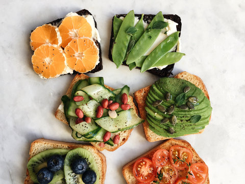 Overhead view of variety of bread toast with toppings for breakfast