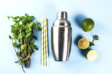 Ingredients for cocktail mojito or lemonade - lemon, lime, mint, sugar, with shaker and cocktail straws. On a light blue background copy space top view