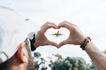 Man showing a heart sign with a plane flying in the middle
