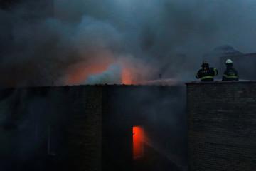 Fire Department of New York (FDNY) firemen work on a six-alarm fire in Manhattan