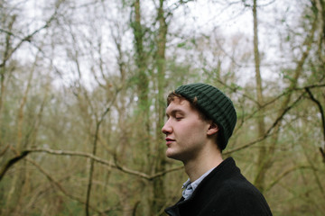 Portrait of young man relaxing in woodland with his eyes closed.