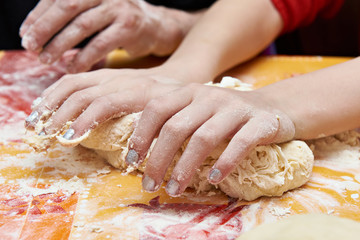 Childrens hands knead dough