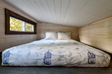 Interior design of a loft bedroom in a tiny rustic log cabin.