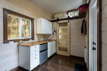 Interior design of a cozy kitchen in a tiny rustic log cabin.
