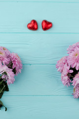 Saint Valentines Day greeting card. Two chocolate hearts and fresh chrysanthemums on blue wooden background, space for text.