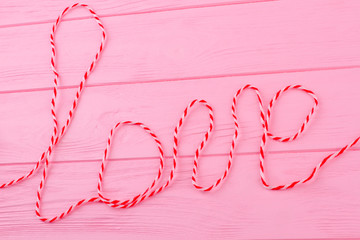Word love on colorful wooden background. Inscription love from red and white woolen thread. Valentines Day and love concept.