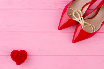 Female red high heels and pearl necklace. Red heart shaped velvet gift box on pink wooden background, copy space. Beautiful composition for Valentines Day.