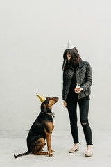 Young woman holding a cupcake while celebrating the dog's birthday